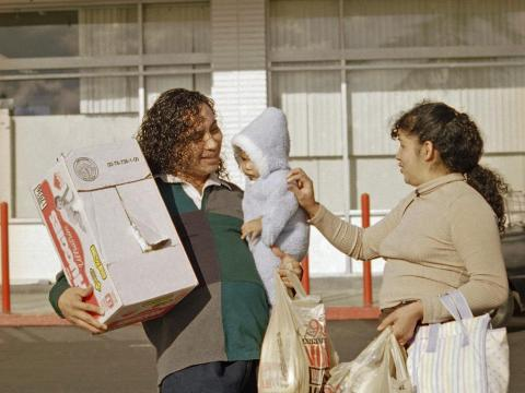Raul Rios (left) and Rosalinda Ramirez (right) attend to their 5-month-old daughter, Angel Mayen, as they leave a Los Angeles Vons grocery store on October 30, 1996.