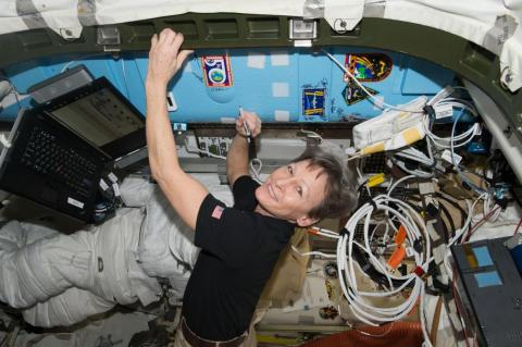 NASA astronaut Peggy Whitson signs a bulkhead on the International Space Station next to the Expedition 50 crew patch in 2017.