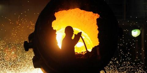 FILE PHOTO: A worker operates a furnace at a steel plant in Hefei
