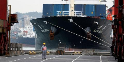 A man stands in front of a cargo ship at a port in the northern Taiwan city of Keelung December 15, 2008.