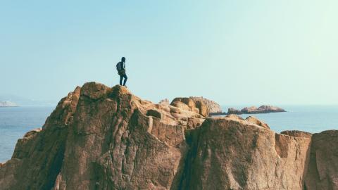 Hombre en acantilado viendo el bonito paisaje, aventura