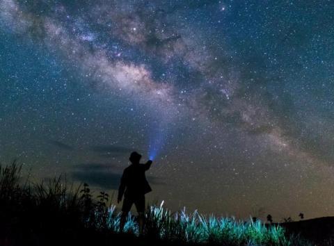 Un hombre ilumina con su linterna el cielo estrellado [RE]