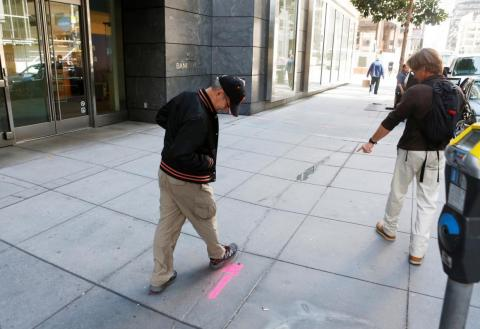 Pedestrians inspect cracks near the sinking Millennium Tower in San Francisco, California.