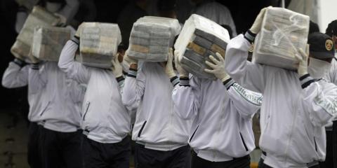 Police officers carry seized cocaine in Lima, Peru, in 2014. A large amount of Peruvian cocaine flowed through China between 2011 and 2015.
