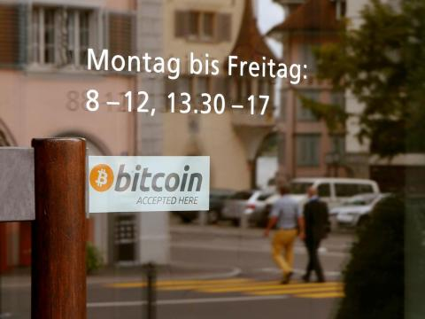 "A sticker reading ""Bitcoin accepted here"" is placed at the entrance of the Stadthaus town hall in Zug."