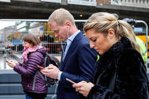 Viajeros mirando sus móviles en Estocolmo, Suecia.