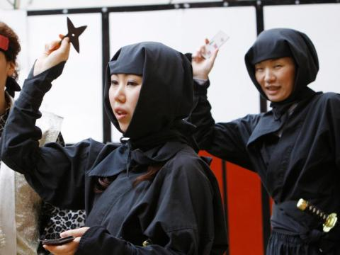 "Women dressed as ninjas throwing ""shuriken"" during a ninja festival in Iga."