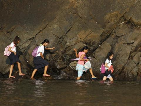 And in Kawag village, an area just north of Manila, in the Philippines, some kids must traverse knee-deep water that edges up to rocky beaches.