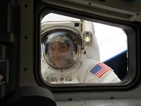 Massimino peers through the flight deck window while refurbishing and upgrading the Hubble Space Telescope in 2009.