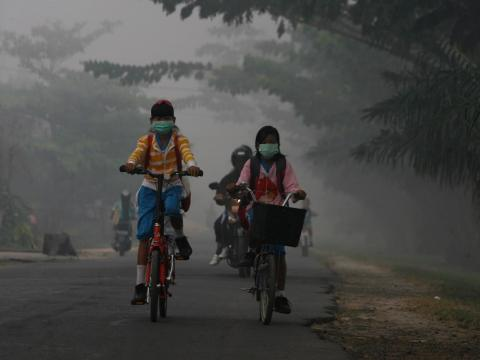 In the Central Kalimantan province of Indonesia, kids ride their bikes through air thick with smog. Air pollution levels have risen steadily in the country in recent years.