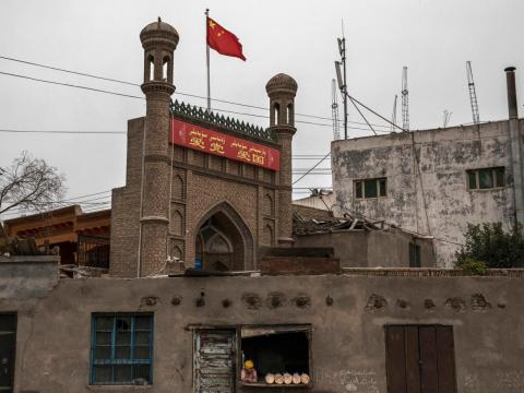 A Chinese flag flies over a local mosque recently closed by authorities as an ethnic Uyghur woman sells bread at her bakery on June 28, 2017 in the old town of Kashgar, in the far western Xinjiang province, China.