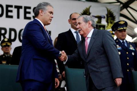 Colombian President Ivan Duque and Defense Minister Guillermo Botero shake hands on August 14, 2018.