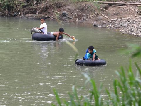 Crossing waterways is common in other parts of the world, too. Children in Rizal province near Manila, Philippines, use inflated tire tubes to cross a river on their way to school.