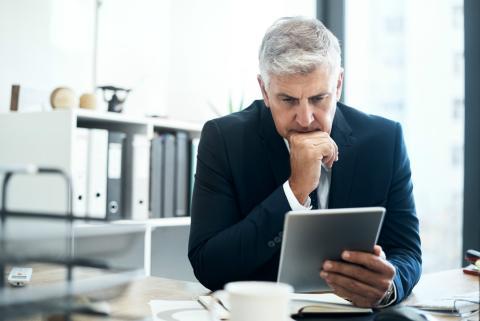 Un ejecutivo mira preocupado las noticias de la subida del IPRF.
