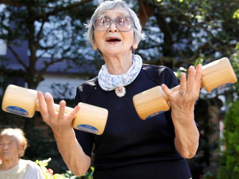 "Elderly and middle-aged people exercise with wooden dumbbells during a health promotion event to mark Japan's ""Respect for the Aged Day"" at a temple in Tokyo's Sugamo district, an area popular among the Japanese elderly, Japan,"