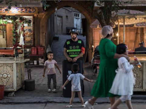 Ethnic Uyghur children joke as they taunt a local police officer on June 29, 2017 in the old town of Kashgar, in the far western Xinjiang province, China.