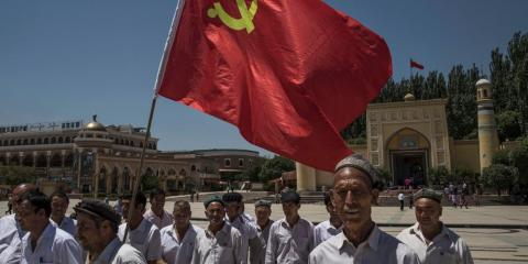 Ethnic Uyghur members of the Communist Party of China carry a flag as they take part in an organized tour outside Id Kah Mosque on June 30, 2017 in the old town of Kashgar, in the far western Xinjiang province, China.