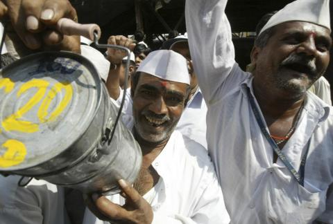A Mumbai lunch delivery man or 'dabbawala' holds up a tiffin box.