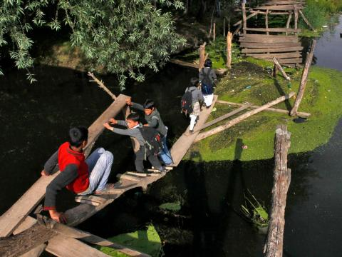 In many regions, a lack of infrastructure means kids must get resourceful. Kids in the Indian state of Kashmir rely on a damaged footbridge to cross the stream.