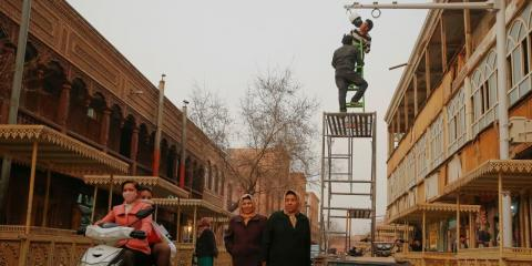Men install a CCTV camera in a shopping street in the old town of Kashgar, Xinjiang Uighur Autonomous Region, China, March 23, 2017.