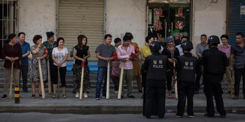 A mix of ethnic Uyghur and Han shopkeepers hold large wooden sticks as they are trained in security measures on June 27, 2017 next to the old town of Kashgar, in the far western Xinjiang province, China.