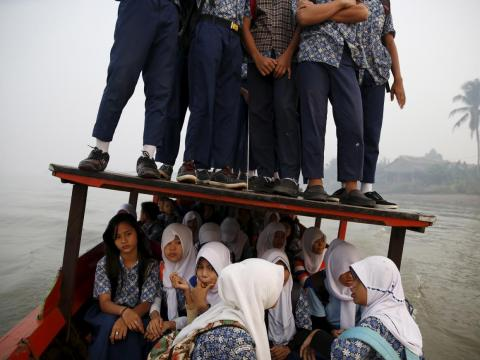 In other parts of the country, the wooden boats that ferry kids across the Musi River sometimes fill up to the extent kids must stand on the roof.