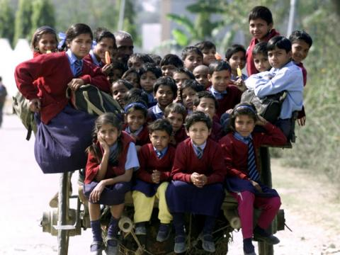 On the outskirts of New Delhi, India, groups of at least 35 children sit together on a horse cart to get home from school.