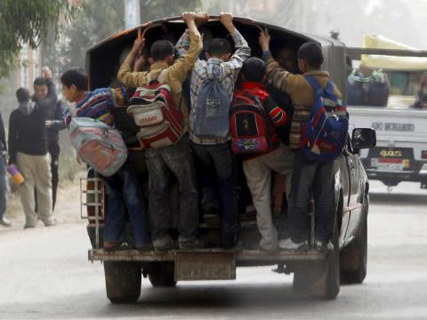 """In parts of Cairo, Egypt, """"school buses"""" involve kids piling into and hanging off the back of ordinary trucks."""