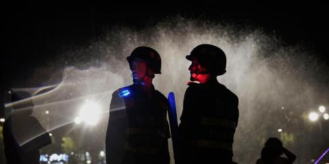 Police officers guard near a new laser and water show that is part of a local government tourism development on June 30, 2017 in the old town of Kashgar, in the far western Xinjiang province, China.