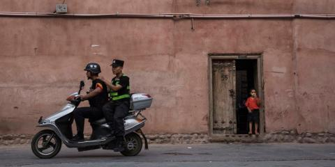 Police patrol on a scooter as an ethnic Uyghur boy stands in his doorway on June 27, 2017 in the old town of Kashgar, in the far western Xinjiang province, China.