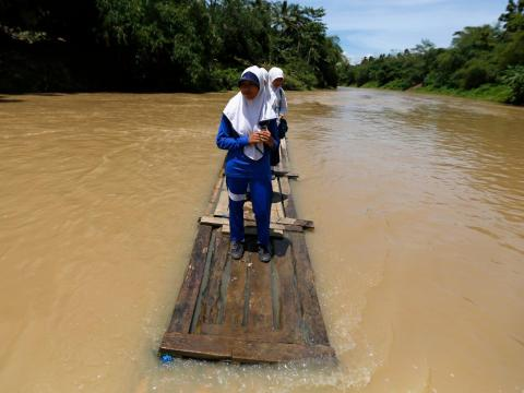 Some bridges on the Ciherang river in Banten province can't be crossed due to flooding, so students use bamboo rafts to get home from school.