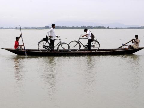 Some children bike to school in the Morigaon district of northeastern India, but heavy rains can flood paddy fields and require the children to travel by boat.