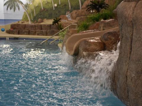 ...Una piscina de 75 pies de largo con tobogán acuático...