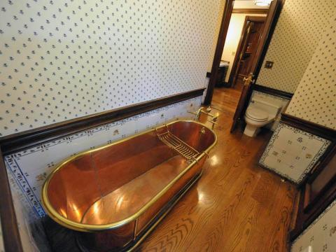 Aquí hay uno de los baños conectados al pasillo. Hay un total de ocho en la residencia principal. Este cuenta con una bañera de cobre [RE]