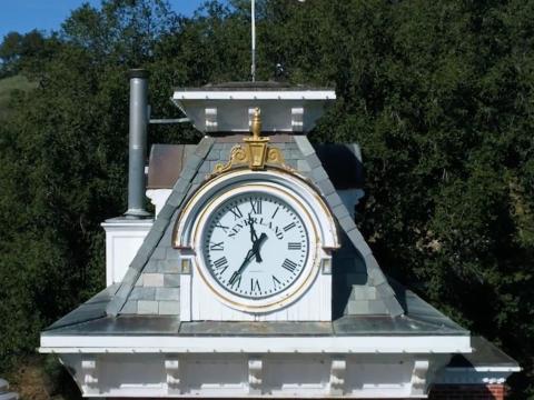 """Aquí hay un gran reloj que se encuentra encima de la estación de tren con """"NEVERLAND"""" en grandes letras negras [RE]"""