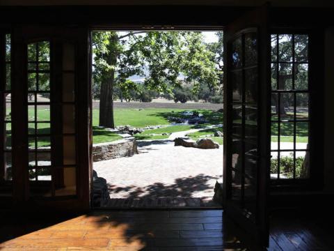 Aquí hay una vista a través de las puertas traseras hacia el patio trasero [RE]