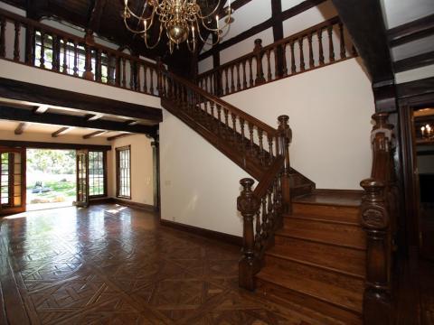 Al bajar las escaleras hacia el primer piso, verás puertas que cruzan la entrada principal que te llevarán a los fondos del rancho [RE]