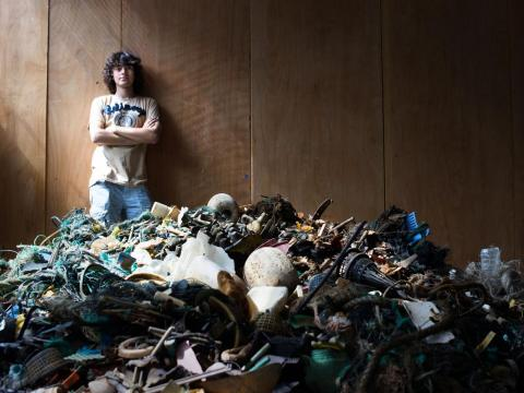 Boyan Slat standing behind a pile of ocean plastic. The material was collected by volunteers in Hawaii, and has been used for recycling research.