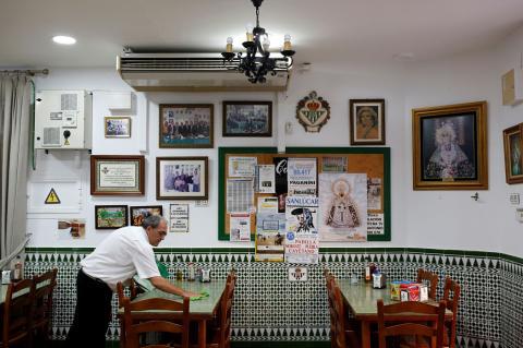 Un camarero prepara las mesas de un restaurante en Chipiona (Cádiz)