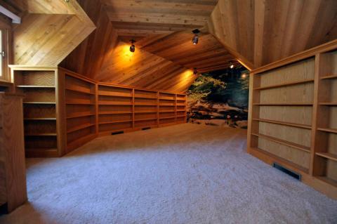 Caminar por un pasillo llevará a otro dormitorio. Este tiene alfombras blancas y las paredes están cubiertas con estantes [RE]