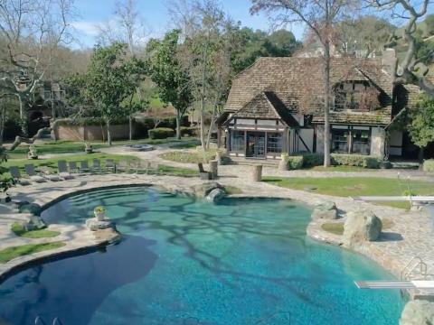 Cerca de los lagos se encuentra una piscina estilo laguna de 14 pies de profundidad y una casa junto a la piscina y el pabellón de tenis [RE]