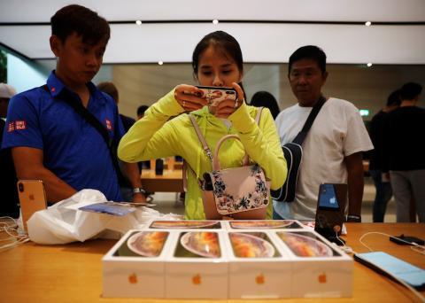 Clientes de vietnam toman fotos del iPhone XS en una Apple Store de Singapur