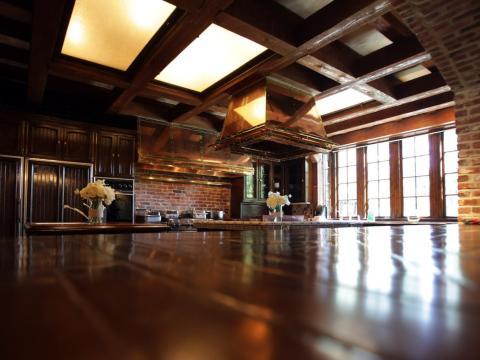 La cocina extragrande tiene ventanas grandes para recibir la luz solar natural que se refleja en las encimeras de madera pulida [RE]