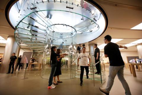 Los empleados aplauden a los primeros clientes de una Apple Store en Pekín
