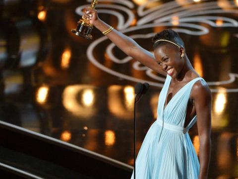 """Lupita Nyong'o recoge el premio a la mejor actriz de reparto en el filme """"12 años de esclavitud"""", en la ceremonia de los Oscars de 2014, en Los Ángeles."""
