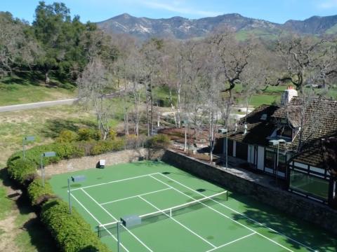 Al lado de la casa de la piscina hay una cancha de tenis iluminada y hundida con un área de visualización [RE]