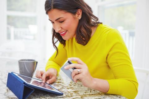 Una mujer consulta en su tablet su cuenta de banco online.