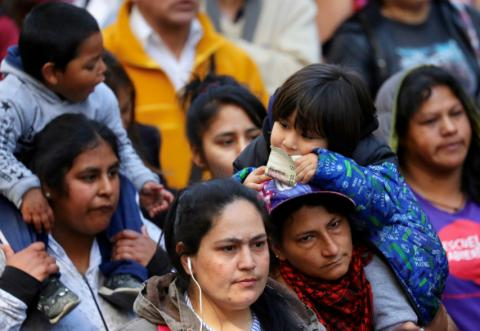 Niño con un billete de peso argentino