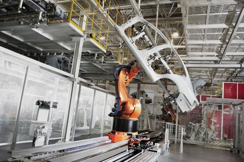 Un robot desplaza una carrocería en una planta automovilística