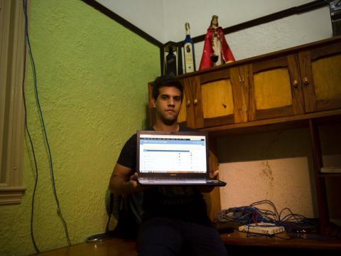 Rafael Antonio Broche Moreno posa con su ordenador, módem y su red por cable en su casa de La Habana.